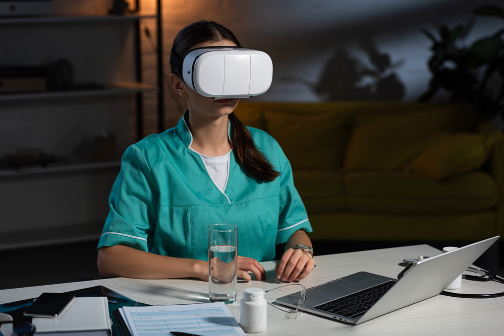 Nurse in uniform with virtual reality headset sitting at table during night shift